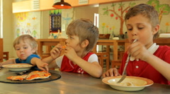 Three kids boys eating in children's cafe Stock Footage