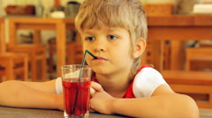 Little boy drinking juice through a straw in the cafeteria Stock Footage
