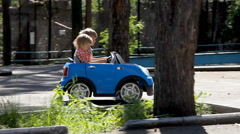 Little boys driving big toy car and having fun, outdoors. - stock footage