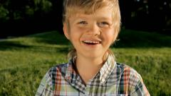 Happy child boy laughing outdoors in spring park Stock Footage