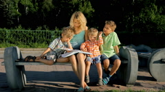 Mom and her kids reading a book outdoors Stock Footage