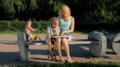 Little boy learning to read with his mother outdoors in park Stock Footage
