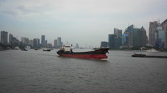 Freight ships sailing on Huangpu river, passing by Pudong financial center Stock Footage