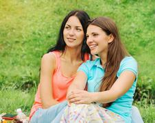 Two happy smiling women friends on picnic at the park Stock Photos
