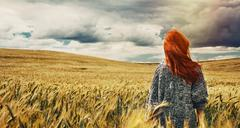 fashion young red hair woman standing back outdoor on breathtaking view of dr - stock photo