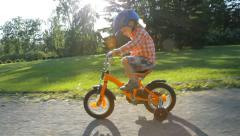 little child in helmet riding bicycle with training wheels in the park - stock footage