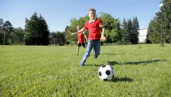 Cute young boys playing soccer in the garden on a bright summer day. Stock Footage