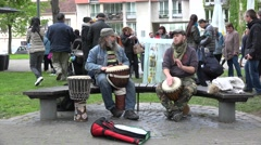 Men play rhythm with wooden drums and people outdoor. 4K - stock footage