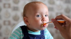 Mum Feeds the Child with a Spoon - stock footage