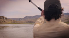 Man paddling down the Missouri river in Montana wearing a baseball hat Stock Footage