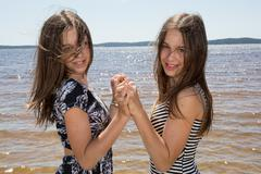 Attractive twins sisters. Close up of two beautiful smiling young women stand Stock Photos