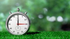 Silver chronometer on green grass Stock Illustration