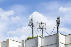 Cell Phone Towers on Resident Building Roof with Blue Sky - stock photo