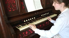 Woman in vintage outfit playing an old piano organ - stock footage