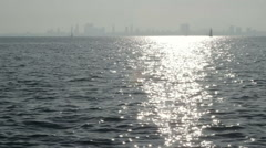Sun glistens on the water, sailboat and city on horizon - stock footage