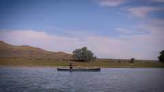 A lone man in a canoe paddles down an empty calm river in the summer Stock Footage