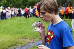 Superman icon and  young man inflates a bubble - stock photo