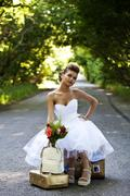 Beautiful redhead bride with suitcases Stock Photos