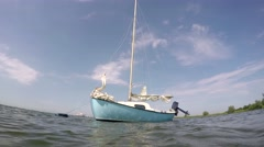 Light blue cute small sail boat floating around for anchor Stock Footage
