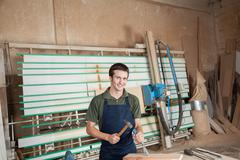 Smiling carpenter working with a chisel Stock Photos