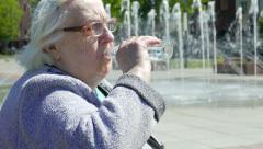 Senior woman drinks water at hot summer day Stock Footage