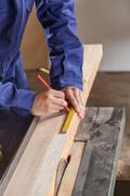 Carpenter measuring a piece of wood Stock Photos