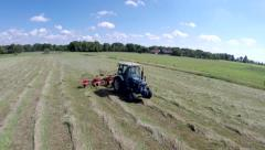 Farmer in tractor mixing turning mowing grass aerial pass very low 4k Stock Footage