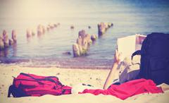 Vintage photo of unrecognizable person reading book on beach. Stock Photos