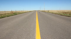 Rural road with yellow line. Low angle, centered shot. Saskatchewan, Canada. - stock footage