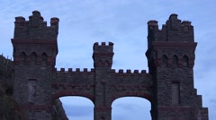 Ominous castle entrance stands before greying sky with clouds - stock footage