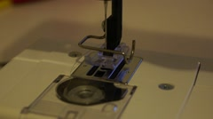 Hand threads the needle of a sewing machine, above the foot and bobbin - stock footage