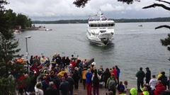 Crowd Welcoming ferry on Ingmarsö - Stockholm archipelago on midsummer day. - stock footage