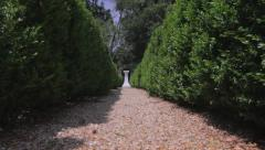 Hedgerow Reveal | Lone white pedestal down the garden path Stock Footage