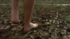 Man Walking on Mud Cracks in the Desert Stock Footage