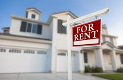 Red For Rent Real Estate Sign in Front of Beautiful House. Stock Photos