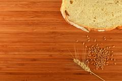 Cutting board with wheat ear, grains and slice of bread - stock photo