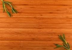 Wooden bamboo cutting board with rosemary leaves - stock photo