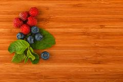 Cutting board with blueberries, raspberries and mint leaves Stock Photos