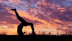 Girl doing acrobatic element at sunset. Slow motion. Stock Footage