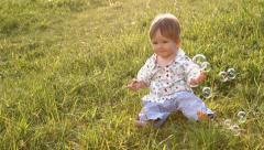 Little boy with soap bubbles. Babe on the lawn. - stock footage