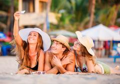 Group of happy young people lying on wite beach sand and taking selfie photo - stock photo