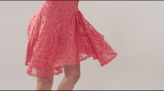 Young woman in pink lace dress dancing against white background Stock Footage