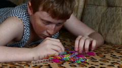 The child spins rubber band loom bracelets Stock Footage