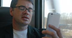 Businessman talks on skype using smartphone Stock Footage