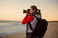 Girl photographer taking pictures with SLR camera at sunset on the beach Stock Photos