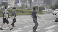 People walk on crosswalk at the Seoul train station Stock Footage