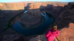 Girl Hiker Standing at the edge of Horseshoe Bend Page Arizona Stock Footage