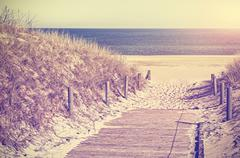 Retro toned photo of a beach path, old film style. Stock Photos