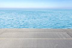 Metal grid floor and blue water background. - stock photo