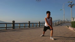 Vietnamese boy does morning exercises on embankment at dawn Stock Footage